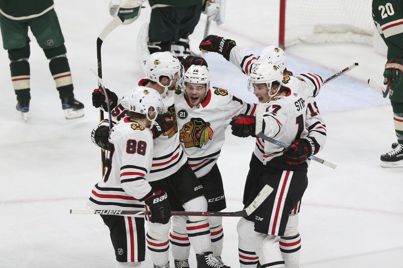 Chicago Blackhawks' Alex DeBrincat, center, and teammates celebrate a goal against the Minnesota Wild during the third period of an NHL hockey game Saturday, Feb. (AP Photo/Stacy Bengs)
