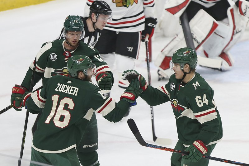 Minnesota Wild's Jason Zucker (16) high-fives teammate Mikael Granlund (64), of Finland, after Zucker scored against Chicago Blackhawks during the first period of an NHL hockey game Saturday, Feb. (AP Photo/Stacy Bengs)