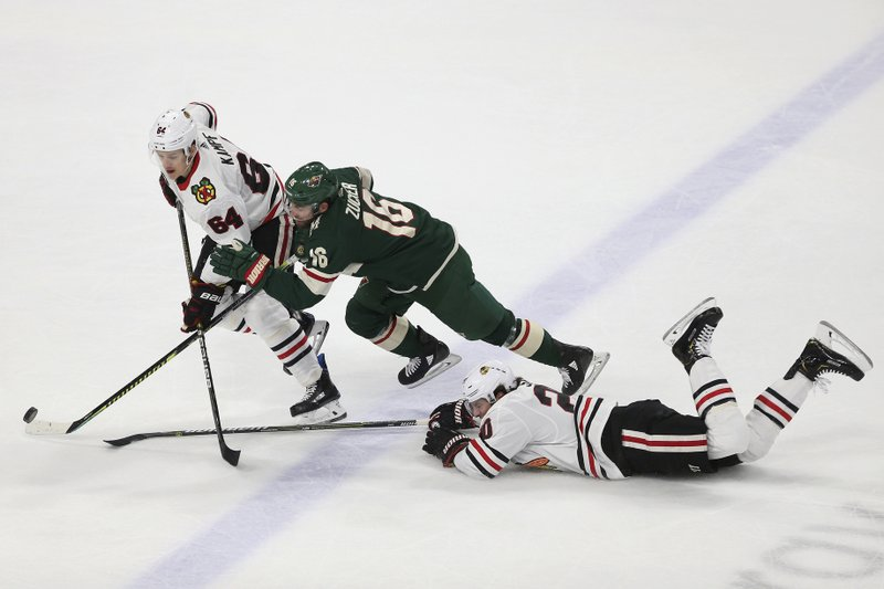 Chicago Blackhawks' David Kampf, left, of the Czech Republic, tries to gain possession of the puck against Minnesota Wild's Jason Zucker during the first period of an NHL hockey game Saturday, Feb. (AP Photo/Stacy Bengs)