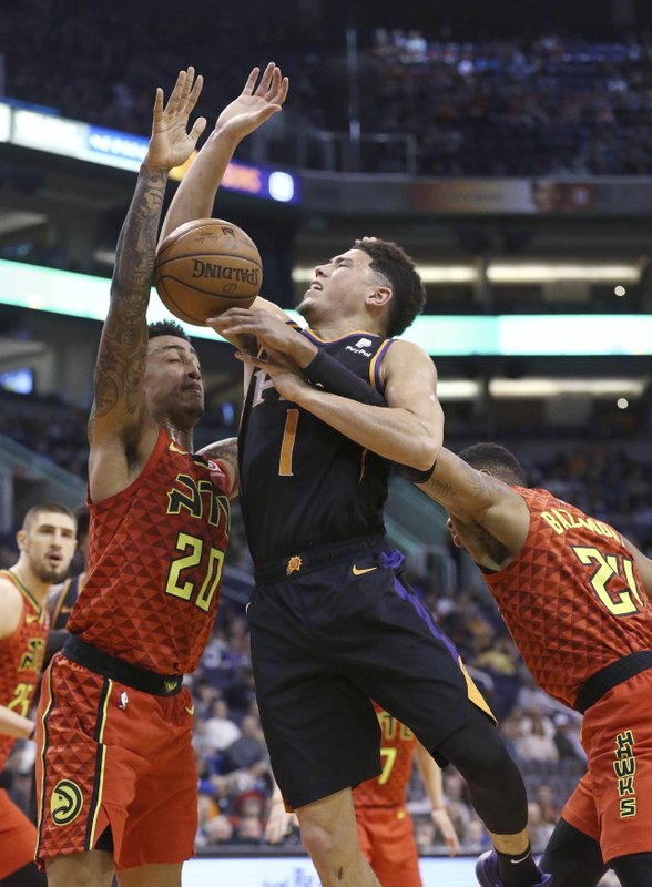 Phoenix Suns guard Devin Booker (1) is fouled by Atlanta Hawks guard Kent Bazemore, right, as Hawks forward John Collins (20) defends during the first half of an NBA basketball game Saturday, Feb. (AP Photo/Ross D. Franklin)