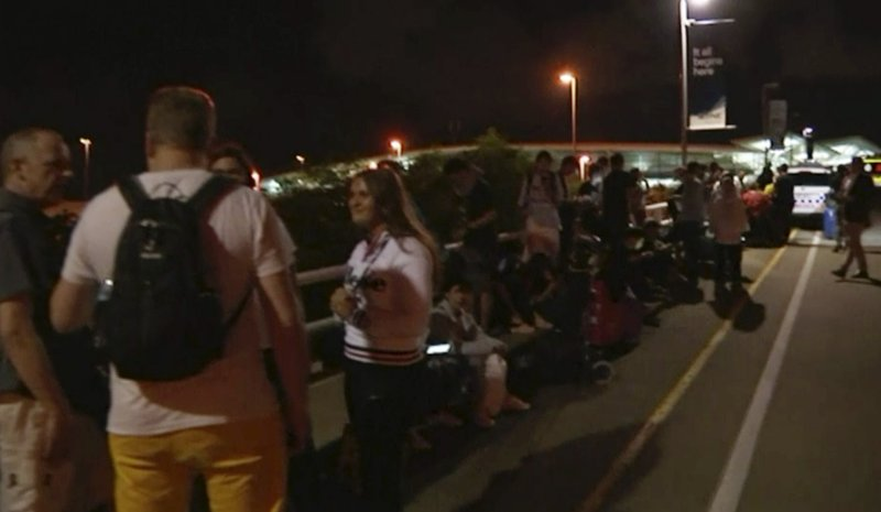 In this image made from a video taken on Saturday, Feb. 2, 2019, travelers stay outside Brisbane International Airport after their evacuation from the airport in Brisbane, Australia. (Australian Broadcasting Corporation via AP)