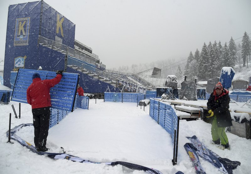 Race officials dismantle the course after an alpine ski, men's World Cup giant slalom was canceled due to weather conditions, in Garmisch Partenkirchen, Germany, Sunday, Feb. (AP Photo/Marco Tacca)