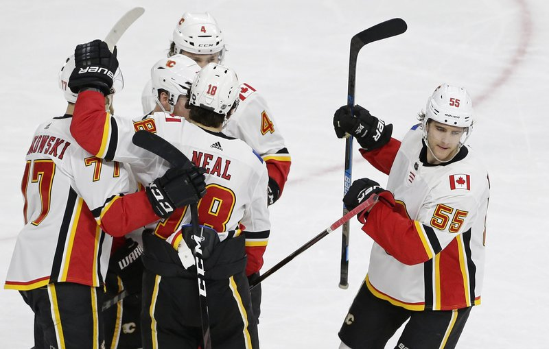 Calgary Flames' Noah Hanifin (55) celebrates with teammates following his goal against the Carolina Hurricanes during the third period of an NHL hockey game in Raleigh, N. (AP Photo/Gerry Broome)