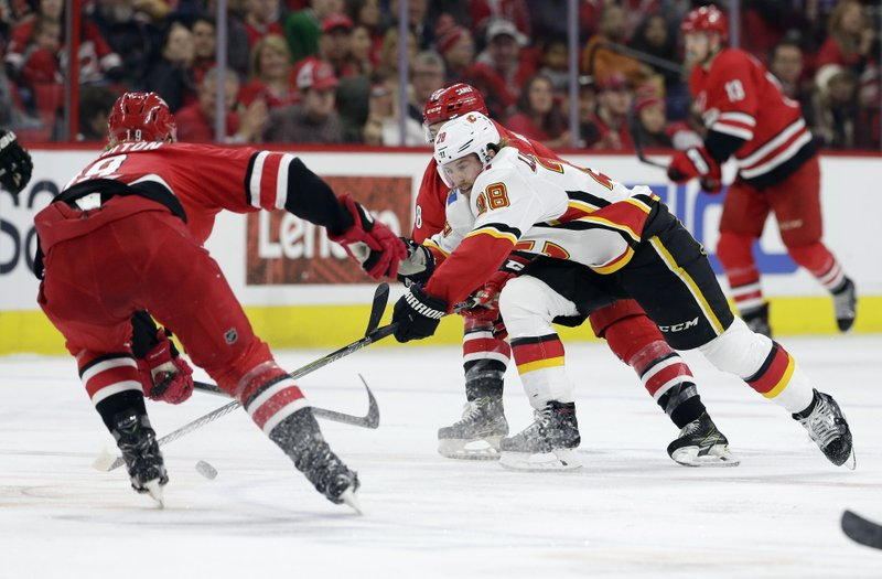 Carolina Hurricanes' Dougie Hamilton, left, and Jordan Martinook chase the puck with Calgary Flames' Elias Lindholm (28), of Sweden, during the second period of an NHL hockey game in Raleigh, N. (AP Photo/Gerry Broome)