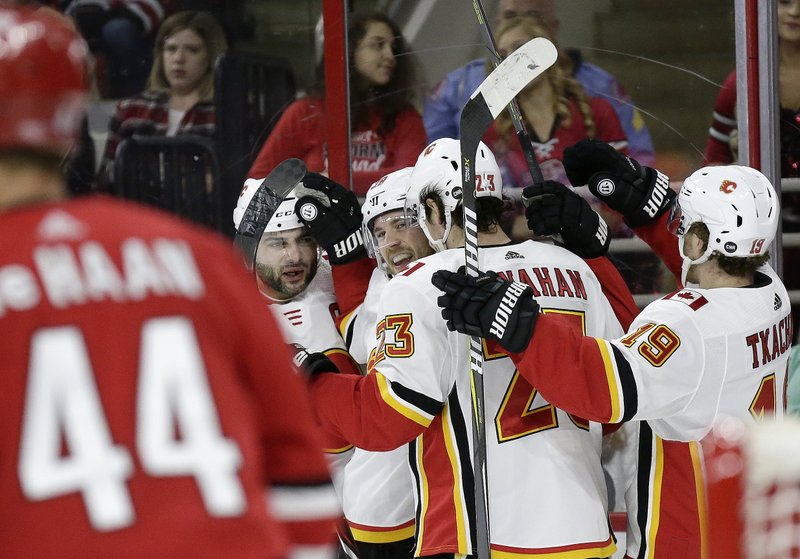 Calgary Flames' Elias Lindholm, center, of Sweden, is congratulated by teammates Mark Giordano, left, Sean Monahan (23) and Matthew Tkachuk (19) following his goal against the Carolina Hurricanes during the first period of an NHL hockey game in Raleigh, N. (AP Photo/Gerry Broome)