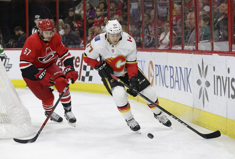 Carolina Hurricanes' Trevor van Riemsdyk (57) chases the puck with Calgary Flames' Mark Jankowski (77) during the first period of an NHL hockey game in Raleigh, N. (AP Photo/Gerry Broome)