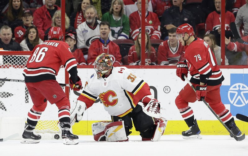 Carolina Hurricanes' Teuvo Teravainen (86), of Finland, scores against Calgary Flames goalie David Rittich while Hurricanes' Micheal Ferland (79) looks on during the first period of an NHL hockey game in Raleigh, N. (AP Photo/Gerry Broome)