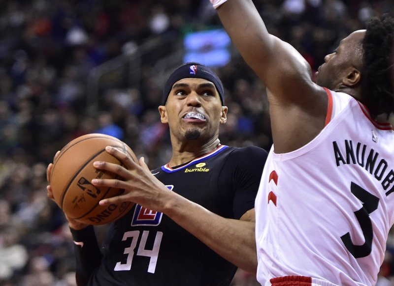 Los Angeles Clippers forward Tobias Harris (34) drives against Toronto Raptors forward OG Anunoby (3) during second-half NBA basketball game action in Toronto, Sunday, Feb. (Frank Gunn/The Canadian Press via AP)