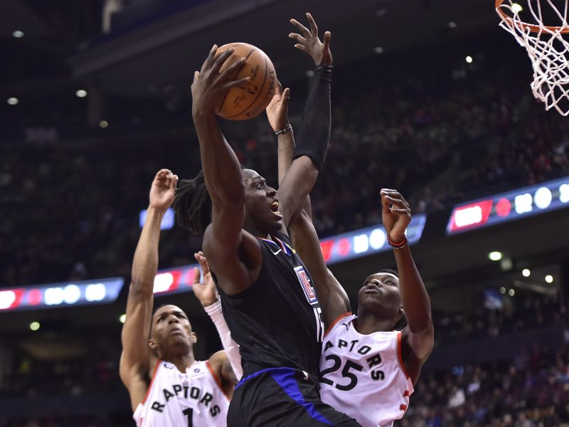 Los Angeles Clippers forward Johnathan Motley (15) goes up to shoot as Toronto Raptors guard Patrick McCaw (1) and forward Chris Boucher (25) defend during second-half NBA basketball game action in Toronto, Sunday, Feb. (Frank Gunn/The Canadian Press via AP)
