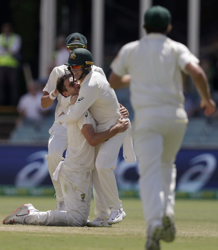 Australia's Pat Cummins, left, celebrates with teammate Marcus Harris after Cummins caught and bowled Sri Lanka's Lahiru Thirimanne on day 4 of their cricket test match in Canberra, Monday, Feb. (AP Photo/Rick Rycroft)