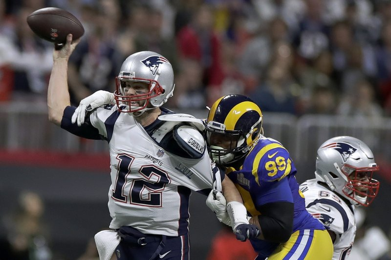 New England Patriots' Tom Brady (12) passes under pressure form Los Angeles Rams' Aaron Donald (99) during the first half of the NFL Super Bowl 53 football game Sunday, Feb. (AP Photo/Carolyn Kaster)