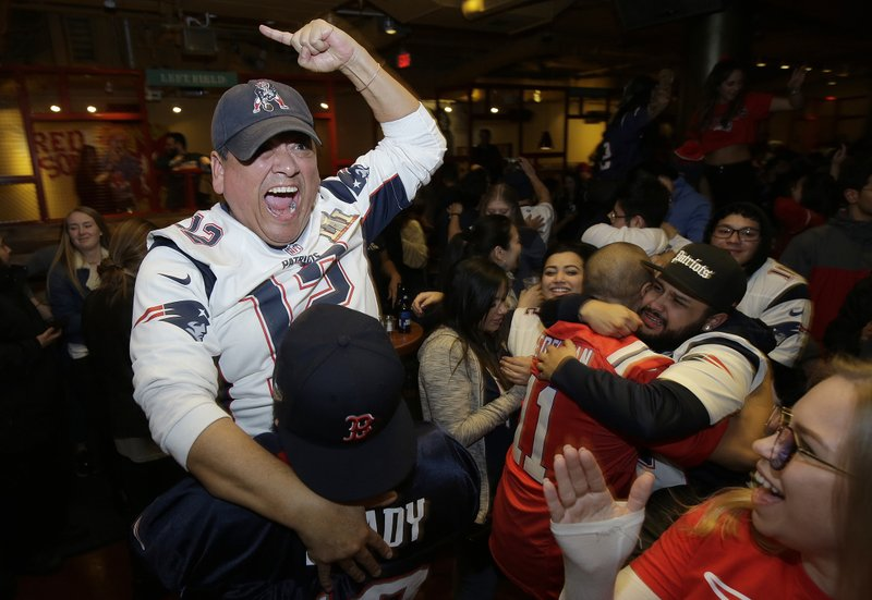 New England Patriots fan Victor Polanco, top, celebrates with others after the Patriots defeated the Los Angeles Rams in the NFL Super Bowl 53 football game in Atlanta at a bar in Boston on Sunday, Feb. (AP Photo/Steven Senne)