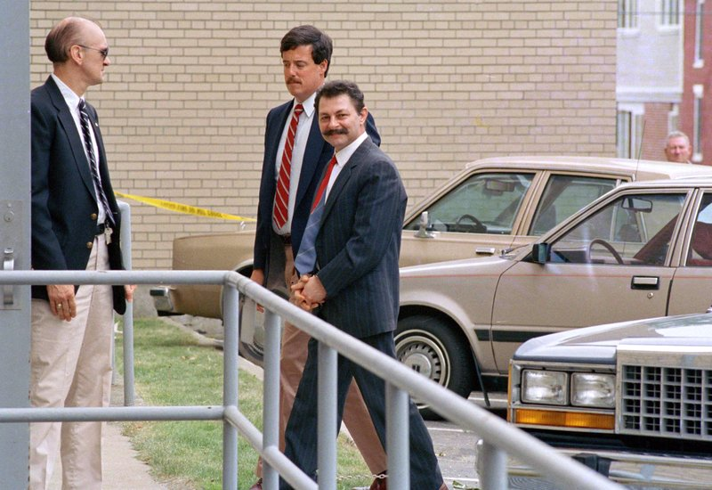 FILE - In this June 22, 1988 file photo, Georges Younan, right, one of three defendants of Lebanese descent from Montreal, Canada, is led into federal court in handcuffs in Burlington, Vt. (AP Photo/Toby Talbot, File)