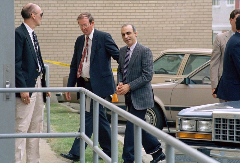 FILE - In this June 22, 1988 file photo, Walid Kabbani, right, one of three defendants of Lebanese descent from Montreal, Canada, is led into federal court in handcuffs in Burlington, Vt. (AP Photo/Toby Talbot, File)