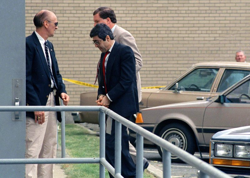 FILE - In this June 22, 1988 file photo, Walid Mourad, center, one of three defendants of Lebanese descent from Montreal, Canada, is led into federal court in handcuffs in Burlington, Vt. (AP Photo/Toby Talbot, File)