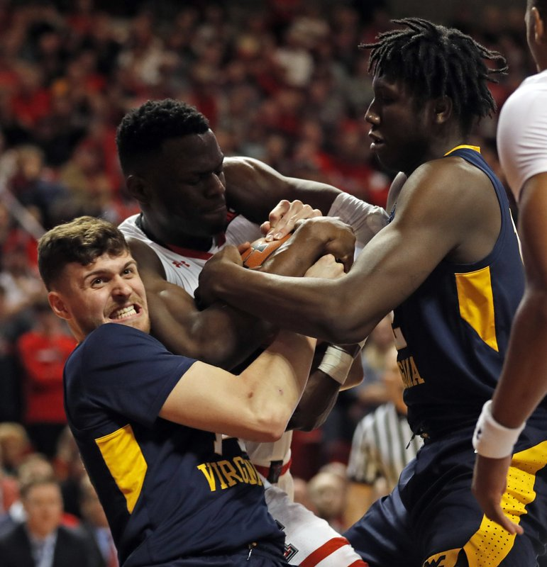 West Virginia's Chase Harler (14), Andrew Gordon (12) and Texas Tech's Norense Odiase (32) fight for control of the ball during the first half of an NCAA college basketball game Monday, Feb. (AP Photo/Brad Tollefson)