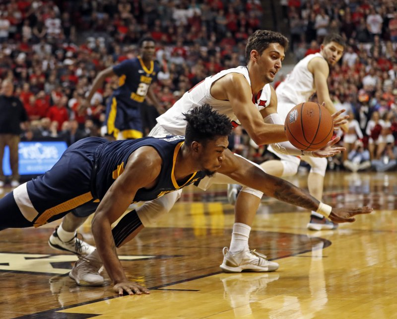 West Virginia's Derek Culver, left, and Texas Tech's Davide Moretti, right, dive for a loose ball during the first half of an NCAA college basketball game Monday, Feb. (AP Photo/Brad Tollefson)