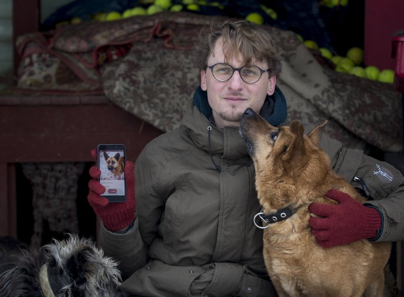 In this photo taken on Saturday, Feb. 2, 2019, Vaidas Gecevicius, who developed an app helping to match stray dogs with potential owners, poses for a picture with a dog and shows this dog's profile on the app in Vilnius, Lithuania. (AP Photo/Mindaugas Kulbis)