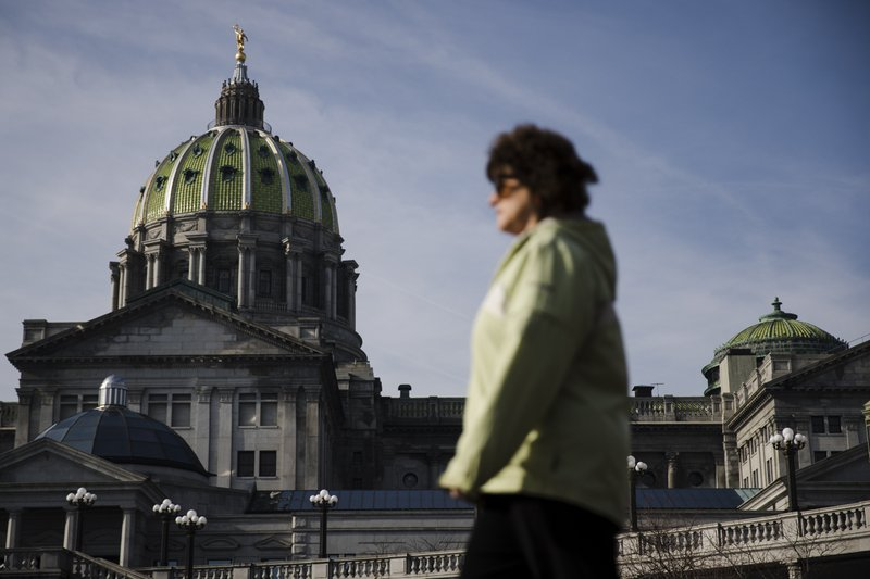 A pedestrian walks past the dome of the Pennsylvania Capitol on the morning of Democratic Gov. Tom Wolf's scheduled budget address for the 2019-20 fiscal year in Harrisburg, Pa. (AP Photo/Matt Rourke)