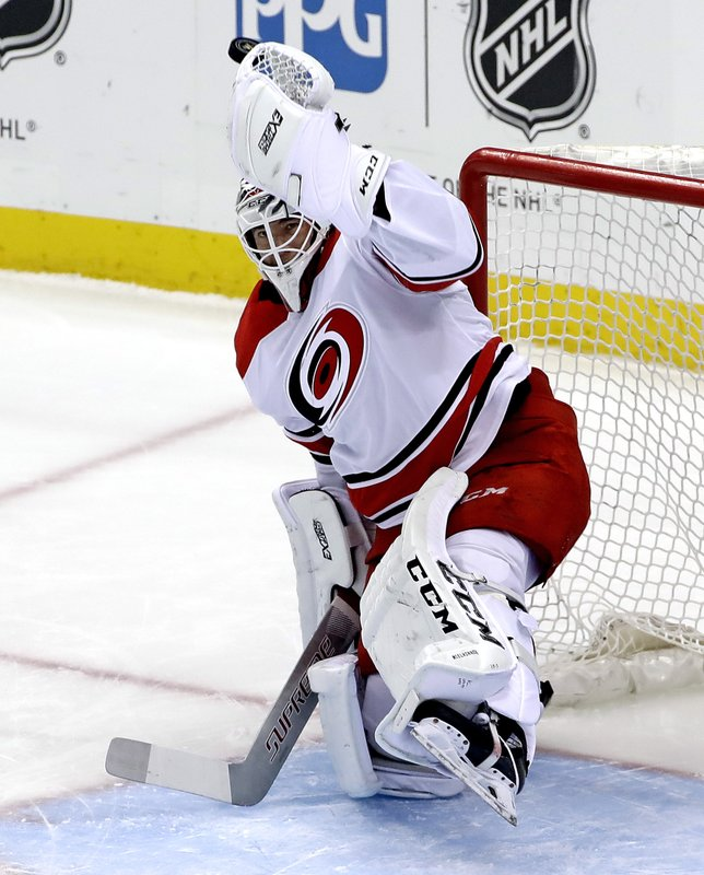 Carolina Hurricanes goaltender Curtis McElhinney deflects a shot with his glove during the first period of the team's NHL hockey game against the Pittsburgh Penguins in Pittsburgh, Tuesday, Feb. (AP Photo/Gene J. Puskar)