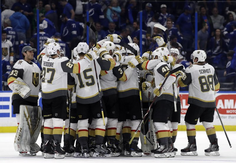 The Vegas Golden Knights celebrate their 3-2 win over the Tampa Bay Lightning during a shootout in an NHL hockey game Tuesday, Feb. (AP Photo/Chris O'Meara)