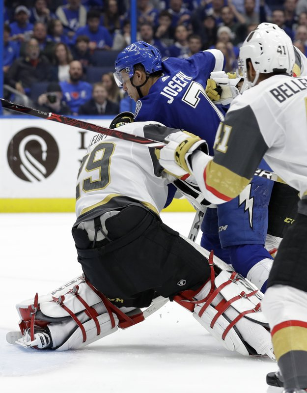 Tampa Bay Lightning right wing Mathieu Joseph runs into Vegas Golden Knights goaltender Marc-Andre Fleury (29) as he scores a goal during the second period of an NHL hockey game Tuesday, Feb. (AP Photo/Chris O'Meara)