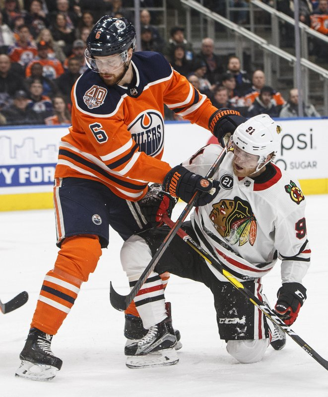 Chicago Blackhawks' Drake Caggiula (91) is checked by Edmonton Oilers' Adam Larsson (6) during the first period of an NHL hockey game Tuesday, Feb. (Jason Franson/The Canadian Press via AP)