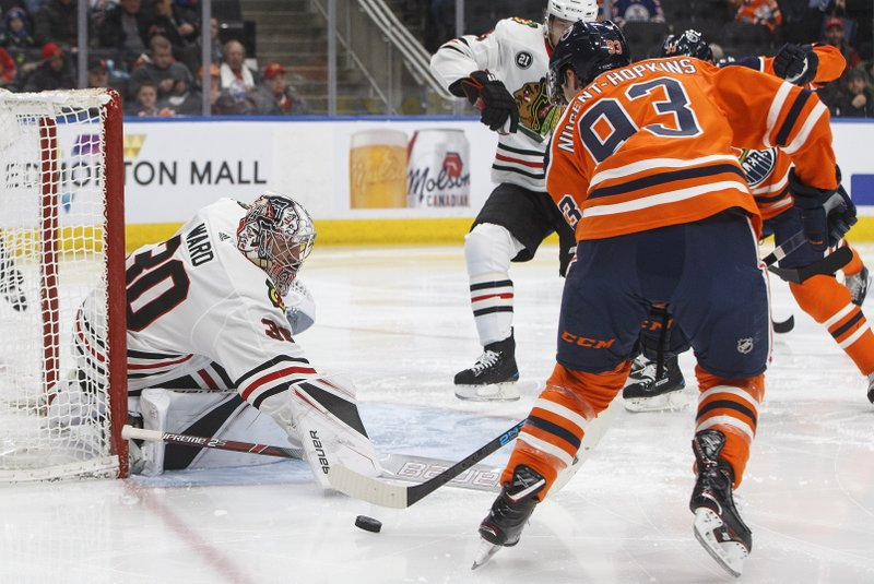 Chicago Blackhawks' goalie Cam Ward (30) makes a save on Edmonton Oilers' Ryan Nugent-Hopkins (93) during the second period of an NHL hockey game Tuesday, Feb. (Jason Franson/The Canadian Press via AP)