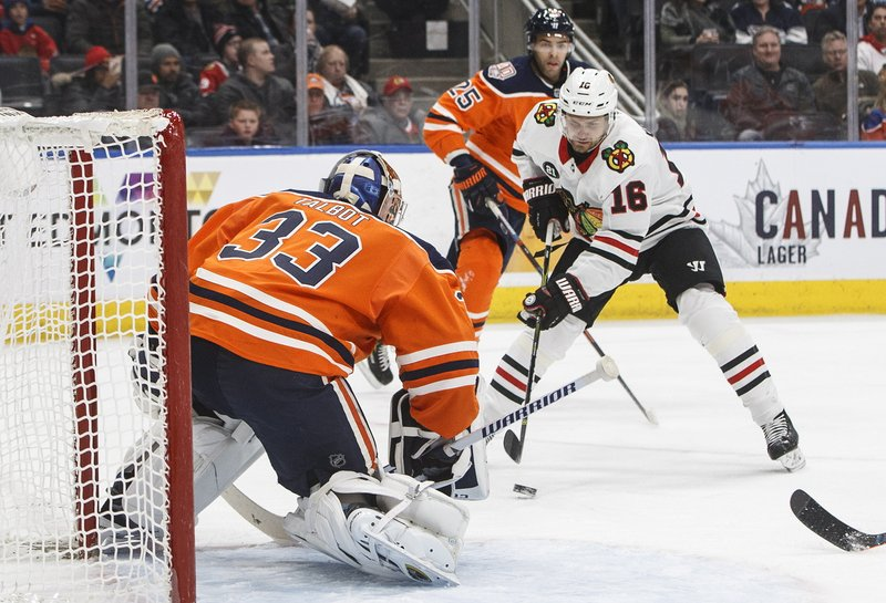 Chicago Blackhawks' Marcus Kruger (16) moves in on Edmonton Oilers goalie Cam Talbot (33) during the first period of an NHL hockey game Tuesday, Feb. (Jason Franson/The Canadian Press via AP)