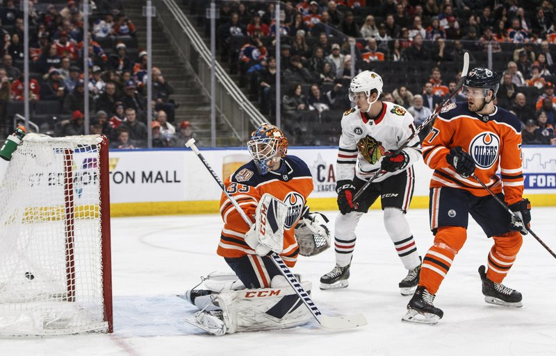 Chicago Blackhawks' Dylan Strome (17) watches the puck go into the net past Edmonton Oilers goalie Cam Talbot (33) as Oscar Klefbom (77) defends during the first period of an NHL hockey game Tuesday, Feb. (Jason Franson/The Canadian Press via AP)