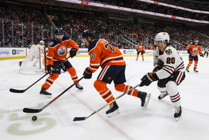Chicago Blackhawks' Brandon Saad (20) chases Edmonton Oilers' Oscar Klefbom (77) as Adam Larsson (6) looks for the pass during the first period of an NHL hockey game Tuesday, Feb. (Jason Franson/The Canadian Press via AP)