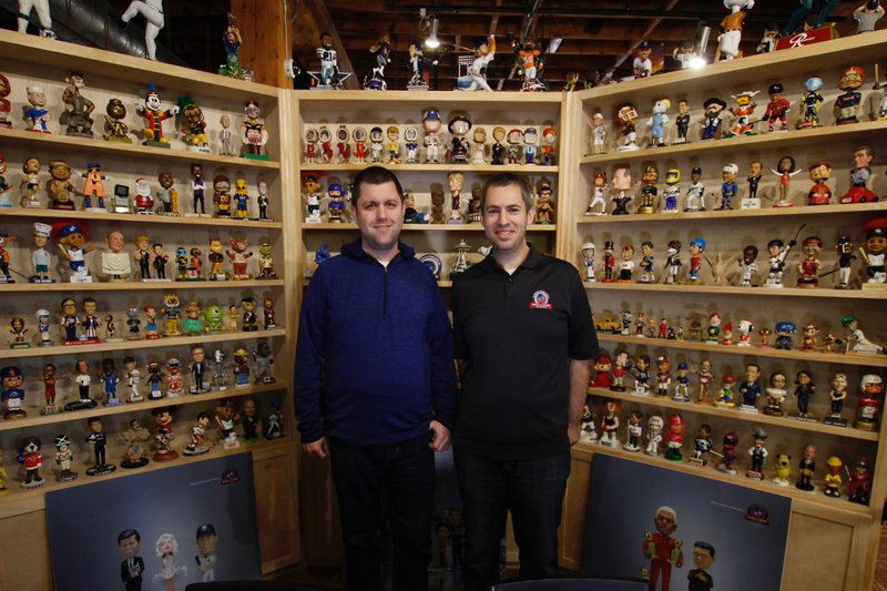 In this Jan. 8, 2019 photo, National Bobblehead Hall of Fame and Museum founders Brad Novak, left, and Phil Sklar, stand near the museum entrance at the National Bobblehead Hall of Fame and Museum in Milwaukee. (AP Photo/Carrie Antlfinger)