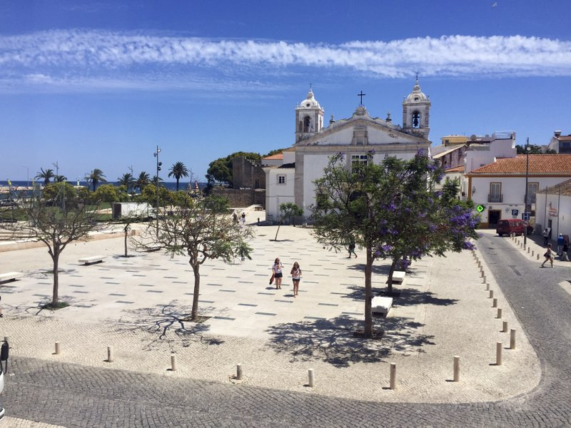 this June 27, 2018 photo, tourists walk through the Infante D. Henrique Square in Lagos, Portugal. Lagos, a striking Portuguese beach town of charming coastlines and slightly sandstone cliffs, is also the birthplace of the African slave trade in Europe. (AP Photo/Russell Contreras)