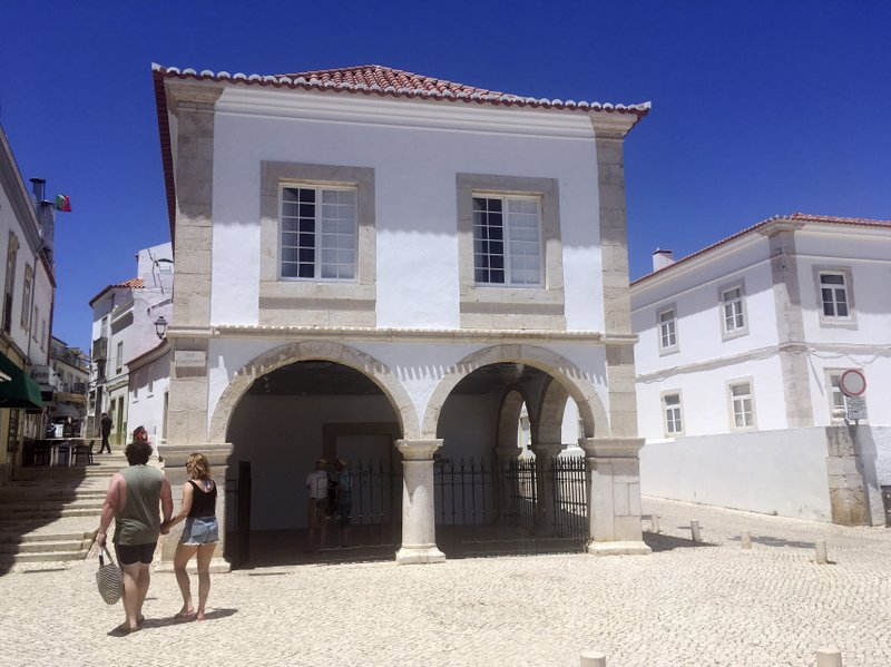 In this June 27, 2018, photo, tourists pass by El Mercado de Escravos, or the Slave Market, which serves as a museum in Lagos, Portugal. (AP Photo/Russell Contreras)