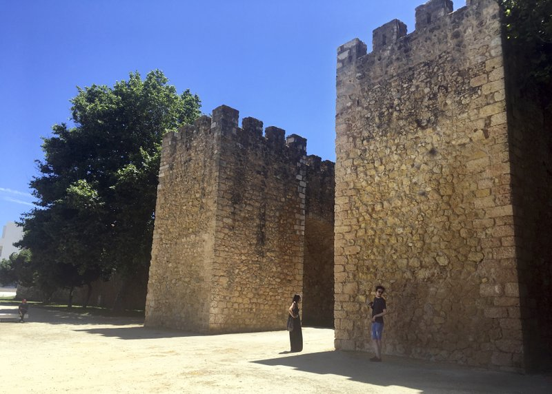 In this June 27, 2018, photo, tourists stand in front of the medieval-era Castle of Lagos in Lagos, Portugal. (AP Photo/Russell Contreras)