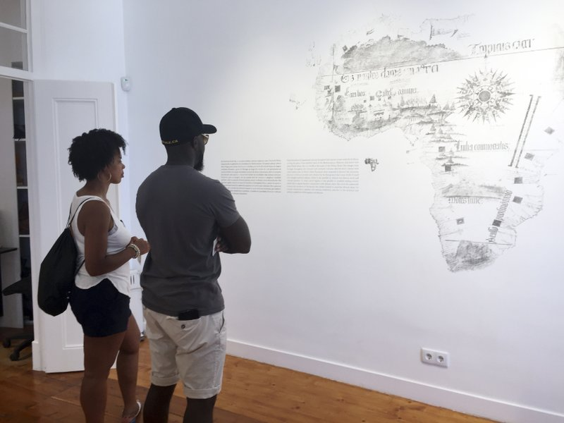 In this June 27, 2018, photo, tourists read about the African slave trade at El Mercado de Escravos, or the Slave Market, a museum in Lagos, Portugal. (AP Photo/Russell Contreras)