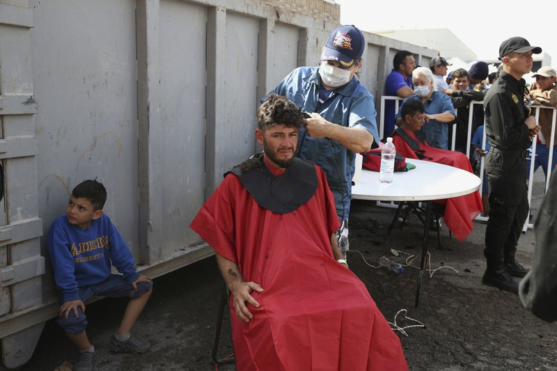 A Central American immigrant gets a haircut at a shelter in Piedras Negras, Mexico, Tuesday, Feb. 5, 2019. (Jerry Lara/The San Antonio Express-News via AP)