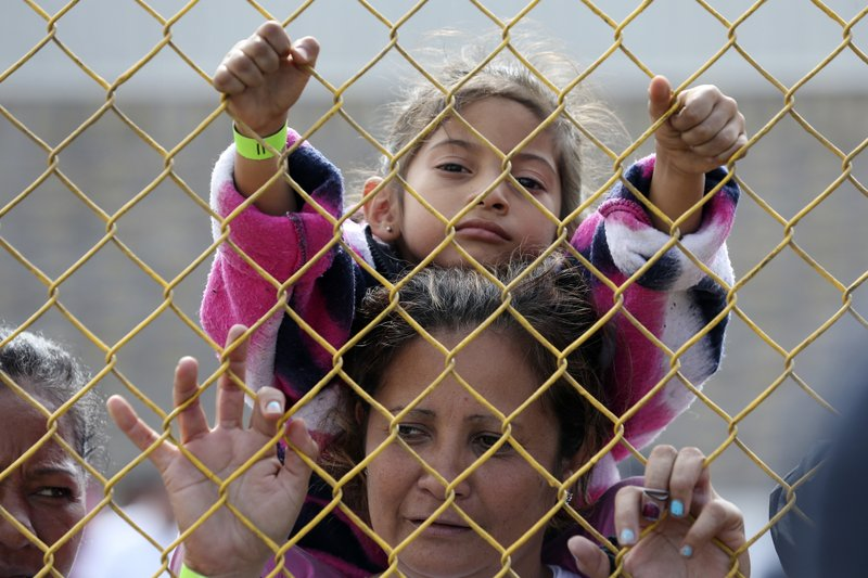 Six-year-old Daniela Fernanda Portillo Burgos sits on the shoulders of her mother, Iris Jamilet, 39, as they look out through the fence of a immigrant shelter in Piedras Negras, Mexico, Tuesday, Feb. (Jerry Lara/The San Antonio Express-News via AP)