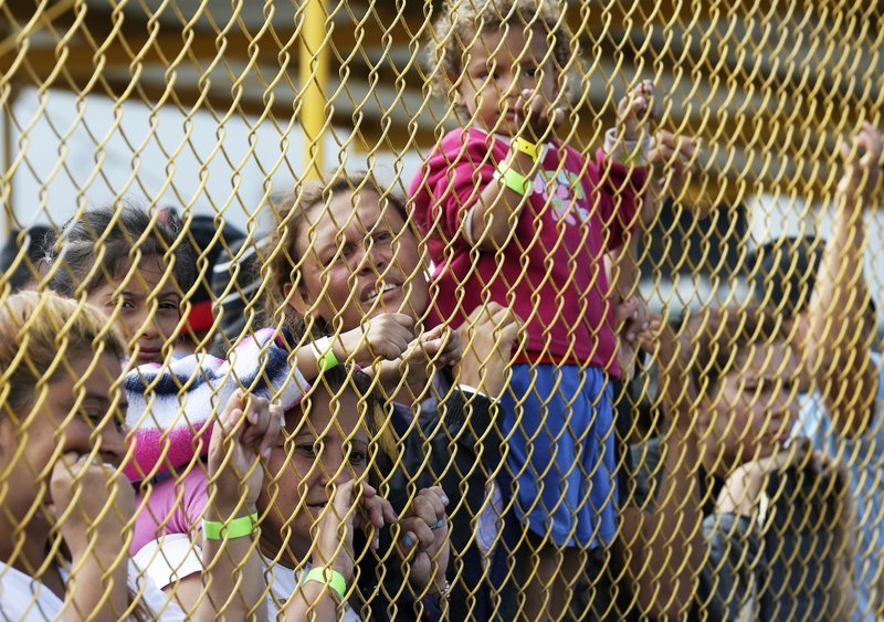 Central American immigrant families look out through the fence of a shelter in Piedras Negras, Mexico, Tuesday, Feb. (Jerry Lara/The San Antonio Express-News via AP)