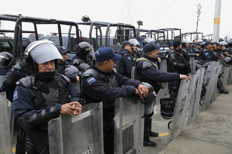 Mexican Federal Police in riot gear guard outside of a migrant shelter for Central American immigrants in Piedras Negras, Mexico, Tuesday, Feb. (Jerry Lara/The San Antonio Express-News via AP)