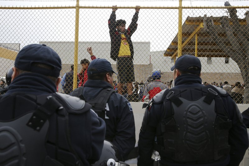 Central American immigrants hang around by the fence line of a shelter guarded by Mexican Federal police in riot gear in Piedras Negras, Mexico, Tuesday, Feb. (Jerry Lara/The San Antonio Express-News via AP)
