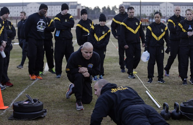 In this Jan. 8, 2019, photo, U.S Army troops observe as instructors demonstrate requirements in the new Army combat fitness test at the 108th Air Defense Artillery Brigade compound at Fort Bragg, N. (AP Photo/Gerry Broome)