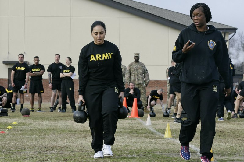 In this  Jan. 8, 2019, photo, U.S Army Staff Sgt. Idis Arroyo,left, carries weights while training to serve as an instructor in the new Army combat fitness test at Fort Bragg, N. (AP Photo/Gerry Broome)