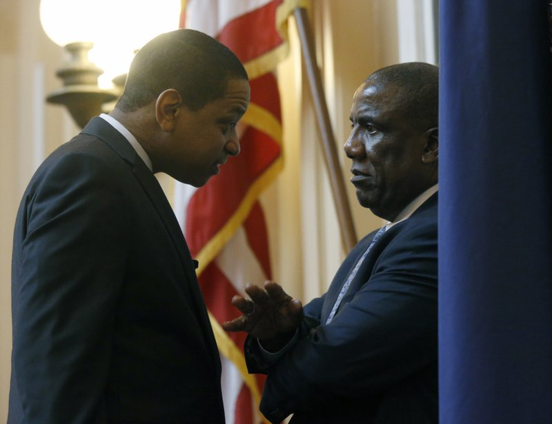 Lt. Gov. Justin Fairfax, left, Sen. Lionell Spruill, D-Chesapeake, , right, confer before the floor session of the Virginia Senate at the State Capitol in Richmond, Va. (Bob Brown/Richmond Times-Dispatch via AP)