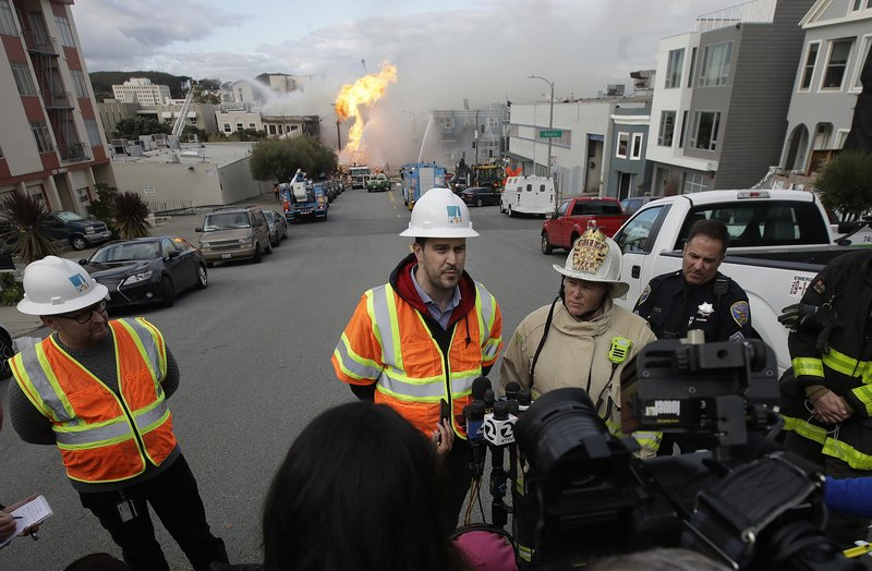 San Francisco fire chief Joanne Hayes-White, second from right, listens as Pacific Gas and Electric spokesperson Paul Doherty, center, speaks to reporters about a fire on Geary Boulevard in San Francisco, Wednesday, Feb. (AP Photo/Jeff Chiu)