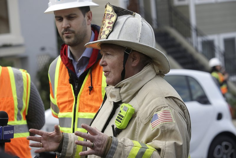 San Francisco fire chief Joanne Hayes-White gestures in front of Pacific Gas and Electric spokesperson Paul Doherty while speaking to reporters about a fire on Geary Boulevard in San Francisco, Wednesday, Feb. (AP Photo/Jeff Chiu)
