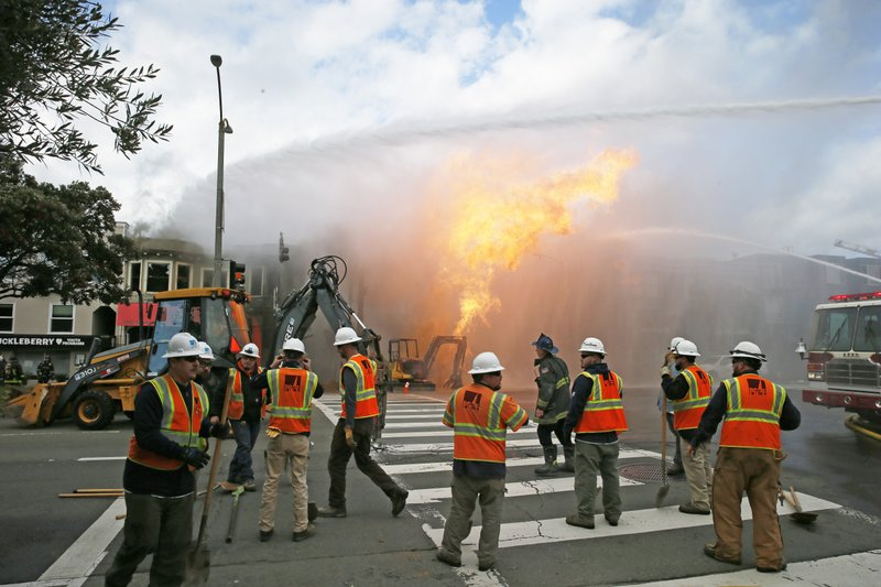 CORRECTS SOURCE TO SAN FRANCISCO CHRONICLE-PG&E officials as firefighters battle a fire following an explosion  Wednesday, Feb. (Santiago Mejia/San Francisco Chronicle via AP)