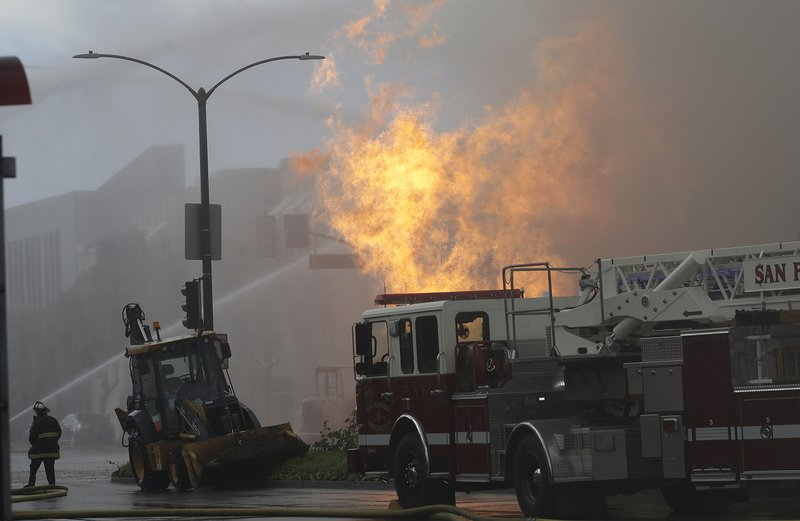 San Francisco firefighters battle a fire on Geary Boulevard in San Francisco, Wednesday, Feb. 6, 2019. (AP Photo/Jeff Chiu)