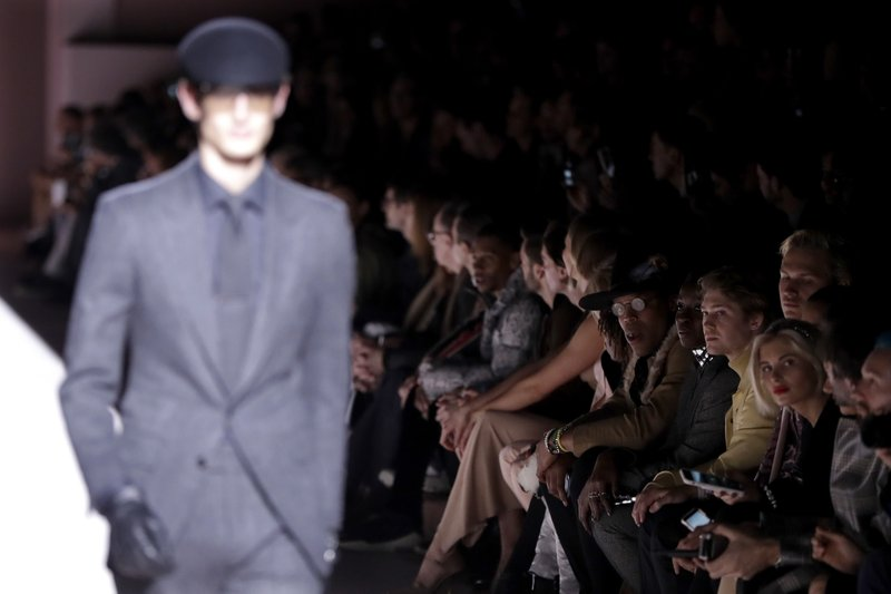 Carolina Panthers quarterback Cam Newton, center right with glasses, watches fashion from the Tom Ford collection displayed by a model on the runway during Fashion Week, Wednesday, Feb. (AP Photo/Julio Cortez)