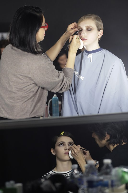 Makeup artists work on a models prior to a show displaying the Tom Ford collection during Fashion Week, Wednesday, Feb. (AP Photo/Julio Cortez)